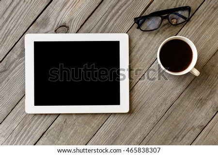 Workspace. White tablet with blank screen in a home office with a cup of coffee and glasses on wooden table, top view
