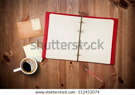 Workspace with coffee cup, instant photos, note paper and notebook on old wooden table - stock photo