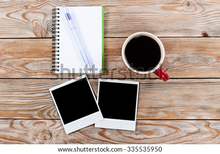 Workspace with coffee cup, instant photos, note paper and notebook on old wooden table. Business concept.