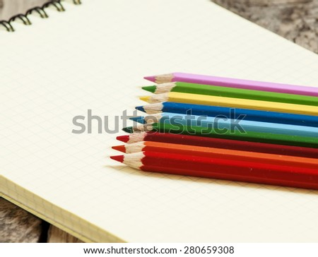 Workspace with colored pencils and notebook on old wooden table