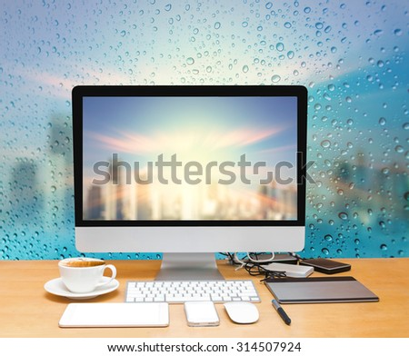 Workspace with computer desktop on the wood table with a glass surface windows with cityscape background