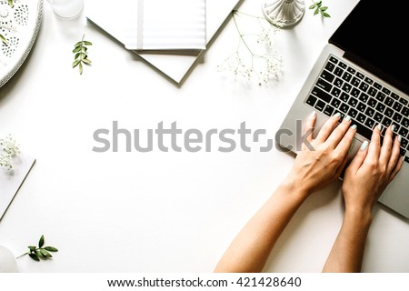 Workspace with laptop, girl's hands, notebook, sketchbook, white vintage tray, candlesticks on white background. Flat lay, top view office table desk. Freelancer working place