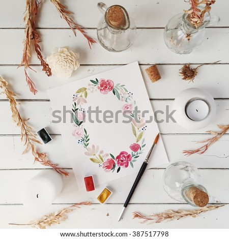 Workspace. Wreath with flowers and leaves painted with watercolor, paintbrush, candles and bottles isolated on white background. Overhead view. Flat lay, top view - stock photo