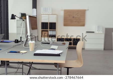 Worktable with Desktop Computer, Cup of Coffee, Notes and Gadgets Inside an Office. - stock photo