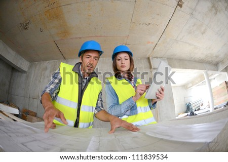 Workteam checking blueprint inside house under construction - stock photo