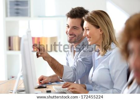 Workteam in office working on desktop computer - stock photo