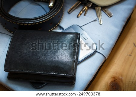 workwear, boots and wallet and mobile on wooden table. - stock photo