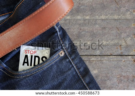 world aids day condom in jeans back pocket with wooden table background, over light