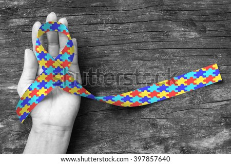 World Autism awareness day WAAD, April 2: Colorful Puzzle fabric ribbon logo color splashed on human hand background raising public support campaign on people's life living w/ mental health illness - stock photo