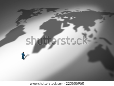 World business strategy and global planning as a person or businessman standing in front of a cast shadow of a global map as a metaphor for company expansion to new markets in exports and imports. - stock photo