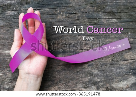 World cancer day, February 4 text message announcement w/ lavender purple colour symbolic ribbons for raising awareness of all kind tumors supporting people living w/ illness - stock photo