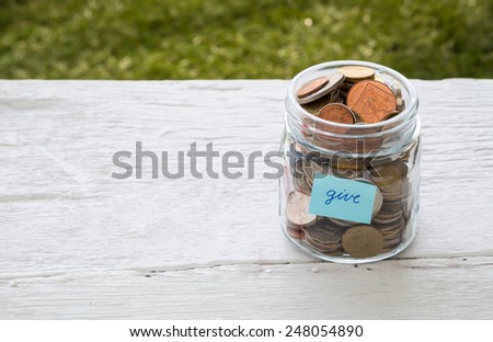 World coins in money glass jar with blue GIVE word label place on white wood table, blank space for text,  donation and charity concept - stock photo