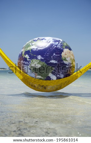 World Cup Brazil globe relaxing in bright yellow hammock above tropical beach sea - stock photo