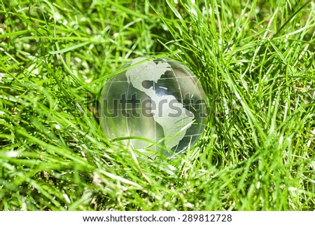 World environmental concept. Crystal globe in green grass. Visible are the continents the Americas. Selective focus. - stock photo