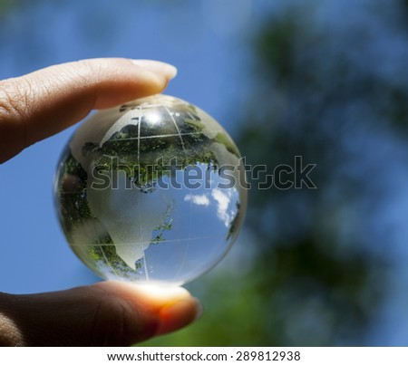 World environmental concept. Crystal globe in human hand on beautiful green and blue bokeh. Visible are the continents the Americas. Selective focus on the reflection