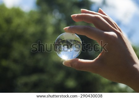 World environmental concept. Crystal globe in human hand on beautiful green and blue bokeh. Visible are the continents the Americas. Selective focus. - stock photo