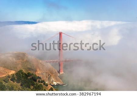 World Famous Golden Gate Bridge Surrounded by Fog  - stock photo