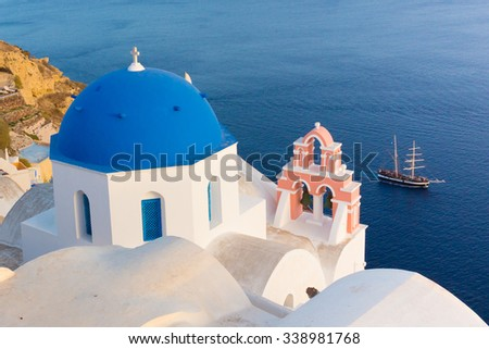 World famous traditional whitewashed chuches and houses of Oia village on Santorini island, Greece. Sunset light. - stock photo