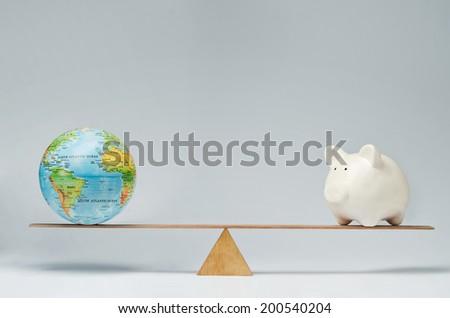 World globe and piggy bank balancing on a seesaw - stock photo