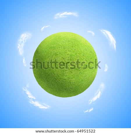World globe as green grass planet with clouds and blue sky background. - stock photo