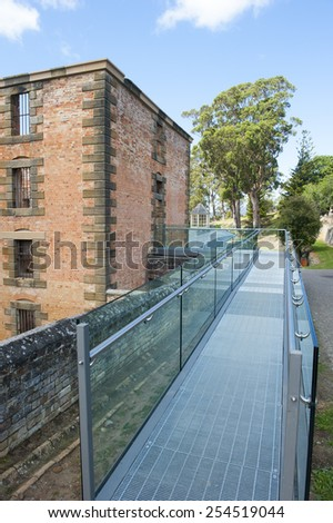 World Heritage Site of  Port Arthur Convict Museum Settlement in Tasmania, Australia, with ruin of historic prison building with new metal gangway. - stock photo