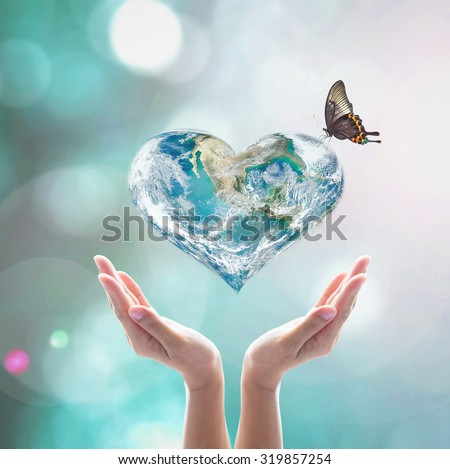 World in heart shape with butterfly over women human hands on blurred natural background green cyan turquoise tree and sky: World Heart health day, CSR concept: Element of this image furnished by NASA - stock photo