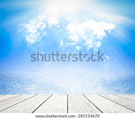 World map of clouds and beautiful blue oceans background and white wooden paving. World Environment Day and World Oceans Day concept. - stock photo