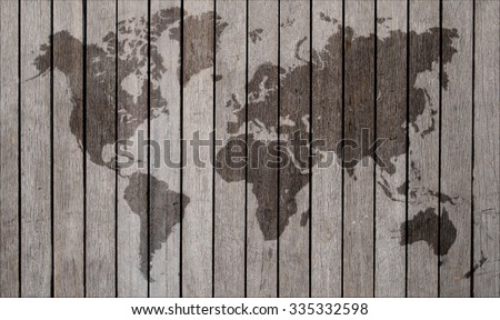 world map overlaid on brown wooden texture patterned background - stock photo