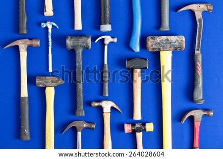 World of hammers with a large assortment of different shapes arranged neatly in vertical lines on a bright blue background in a DIY, carpentry, building, maintenance and renovation concept - stock photo