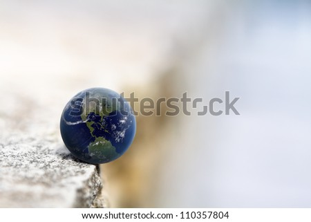 World on the edge of a cliff/ Earth in the balance (Elements of this image furnished by NASA) - stock photo