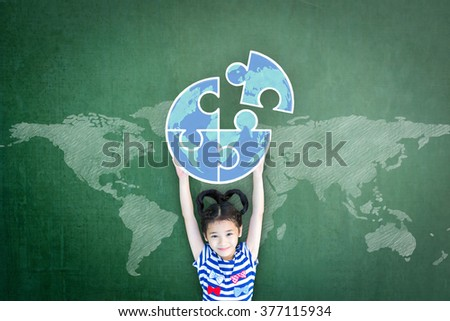 World thinking day WTD concept: Little child kid hand raising jigsaw globe earth freehand doodle creative idea drawing on grunge green chalkboard background with sketchy map backdrop: Happy girl scout - stock photo