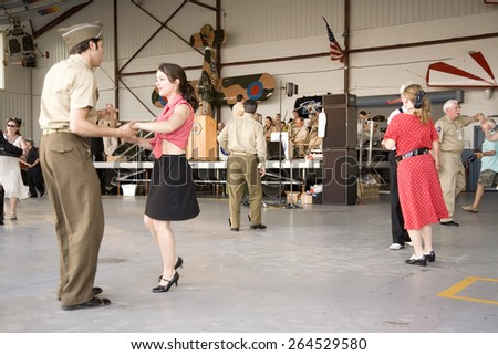 World War II actors dance in airport hanger at Mid-Atlantic Air Museum World War II Weekend and Reenactment in Reading, PA held June 18, 2009 - stock photo