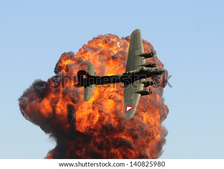 World War II era bomber in front of giant explosion - stock photo