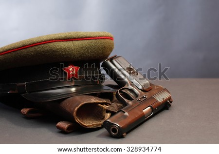 World War II Soviet officer equipment. Military cap near handgun and holster - stock photo