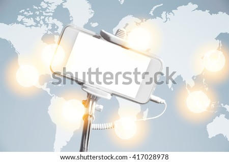 Worldwide communication interface. Visual effects. Mobile phone with copy space for your advertisement. Electronic device on a hand held monopod selfie stick. Technology and communication concept  - stock photo