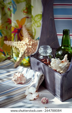 Worldwide trade concept: coffee, wine, cotton fabrics and seashells set as home decorations in a wooden box. Natural light shot. Toned photo. - stock photo