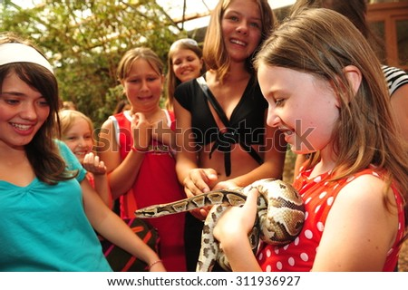 Worms, Germany - Jule 27, 2009 - Kids looking at a royal python in a animal park