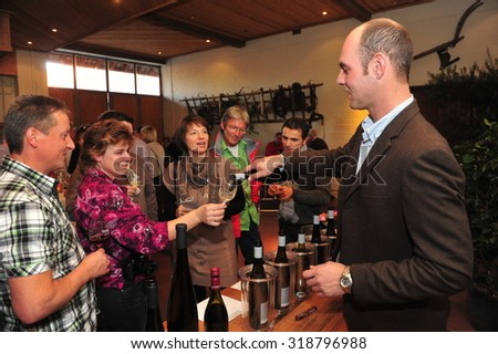 Worms, Germany - November 1, 2010 - People tasting wine and winemaker serving