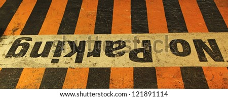 """Worn and aged """"NO PARKING"""" sign on black-yellow cracked asphalt - stock photo"""