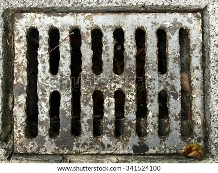 Worn and rusty sewer cover - stock photo