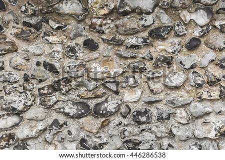 Worn and weathered traditional flint wall background texture. - stock photo