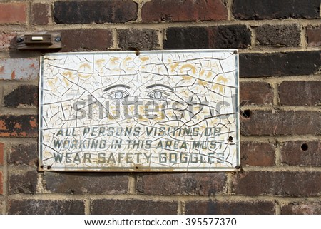 Worn and weathered vintage safety goggles sign on wall of old brick building. - stock photo