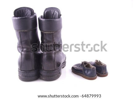 worn black army boots and baby shoes isolated on white background isolated on white background - stock photo
