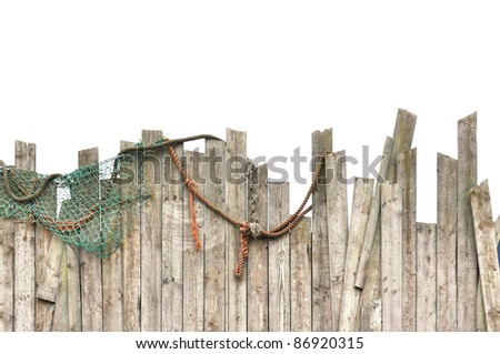 Worn fence with fishnet and ropes on white - stock photo