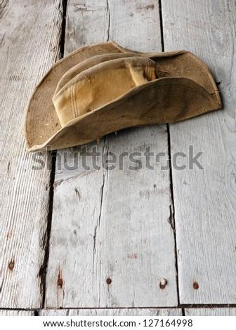 Worn Hat on Weathered Wood - stock photo