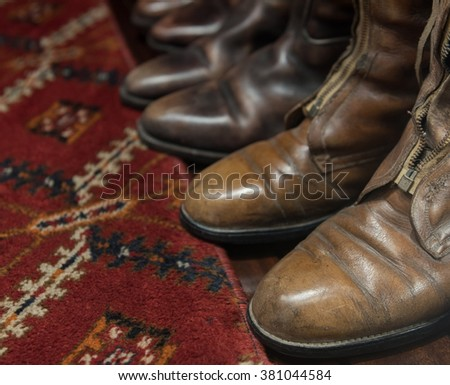 Worn Leather Boots with Patterned Carpet - stock photo
