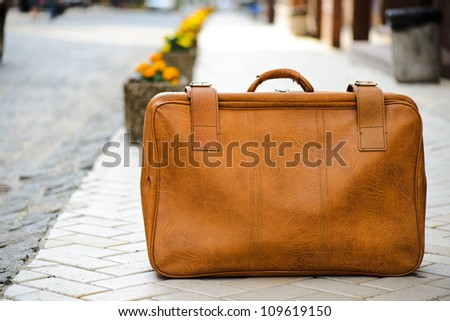 Worn leather suitcase left on a road - stock photo
