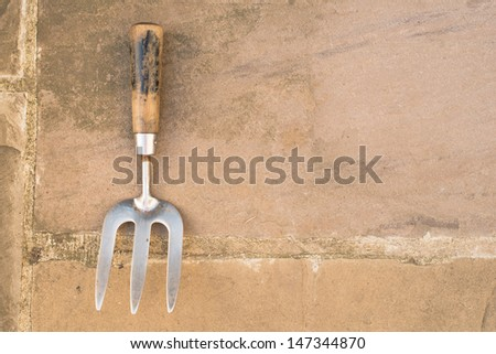 Worn metal and wooden garden hand fork on some patio paving slabs - stock photo