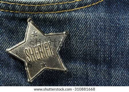 Worn Out Old Sheriff Badge on Blue Denim Horizontal Photograph - stock photo