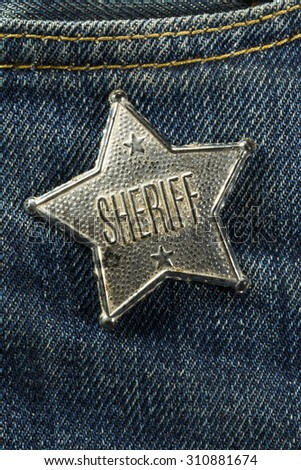 Worn Out Old Sheriff Badge on Blue Denim Vertical Photograph - stock photo